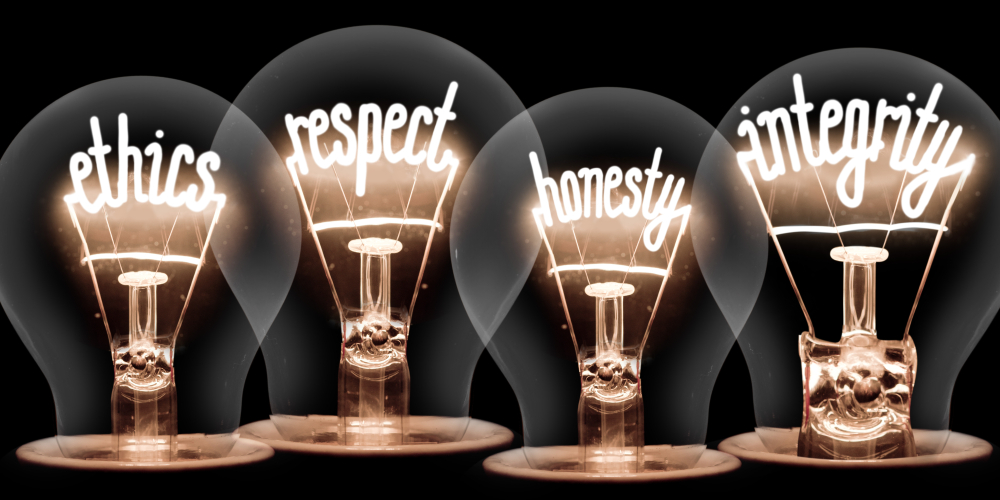 Words respect, ethics, honesty, and integrity lit inside light bulbs