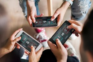 Three friends playing a game on a mobile device